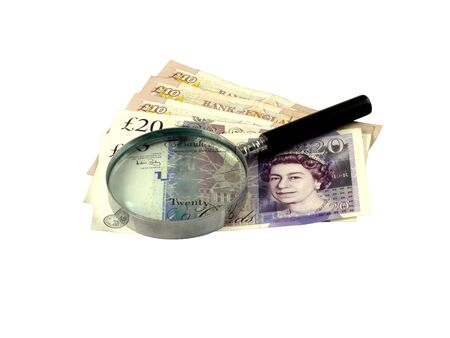 scrutinise: Twenty and Yen Pound Sterling notes with a magnifying glass. Stock Photo