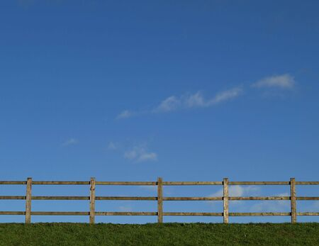 Rail fence on grass bank against blue sky with light clouds Stock Photo