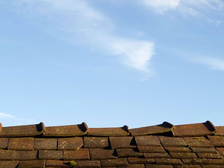 Ein Dach mit gebrochenen Fliesen vor blauem Himmel Hintergrund