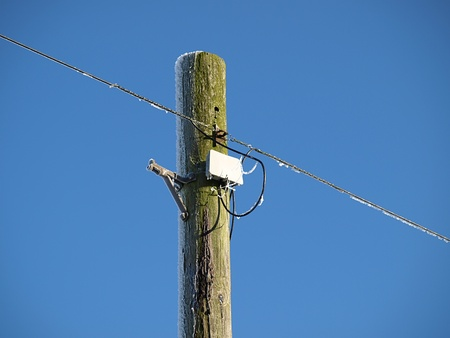 A Telegraph pole with telephone wire in winter