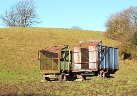Two rusty abandoned farm trailers in field photo