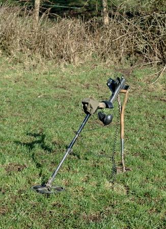 detecting: Metal detector resting on spade in field