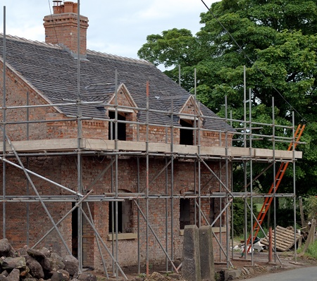 Old country house being renovated with scaffolding in place photo