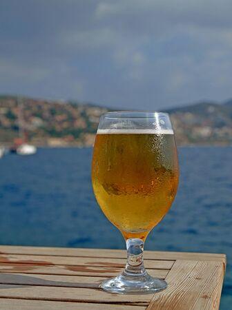 goblet: Cold frosty beer on table at Mediterranean seaside cafe