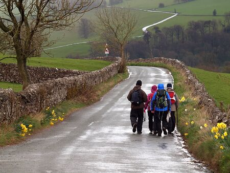Group walking in Peak District Park on a wet spring day Stock Photo