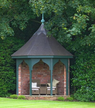 garden summerhouse at the end of lawn surrounded by trees Stock Photo - 14447802