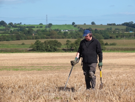 metal detecting in a field of stubble