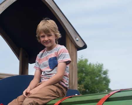 younf male caucasian child on play equipment in playground photo