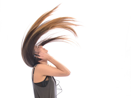 girl with long hair dancing to music on headphones