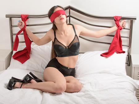 Bondage Frau ins Bett gebunden mit roten Schals