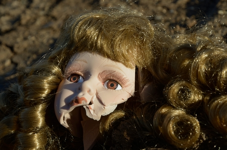 accident dead: Broken head of porcelain doll lying on the ground