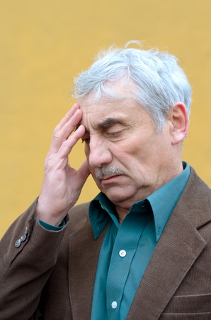 perplex: Stressed caucasian senior man with headache put his hand on his forehead, frowning, looking down. Head and shoulders portrait. Brown corduroy jacket, green shirt, solid yellow background. Stock Photo