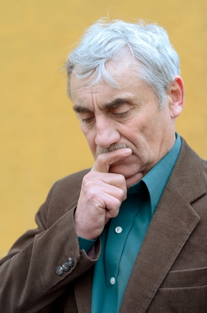 corduroy: Concerned caucasian senior man with his hand on his chin pondering, frowning, looking down. Head and shoulders portrait. Brown corduroy jacket, green shirt, solid yellow background.