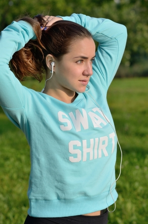 medium closeup: A medium closeup portrait of a young caucasian woman with green eyes fixing her hair in a ponytail while gazing away. The model is wearing a sport blue sweatshirt and black shorts. Sunset lighting.