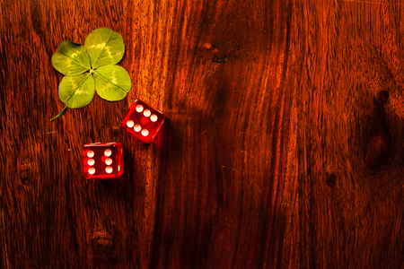 Two red dices with a luckycharm four-leaf clover Stock Photo