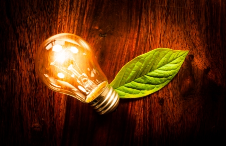 Bright light bulb with a green leaf at a wooden table