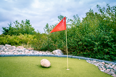 Large minigolf cource with a flag in the hole photo