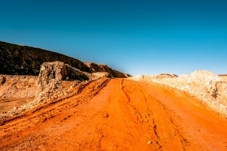 Orange road going through a canyon