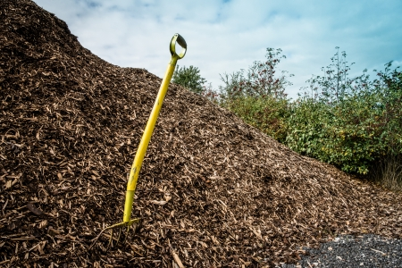 Yellow shovel in a big pile of mulch