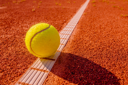 Yellow tennisball on the line at a clay court