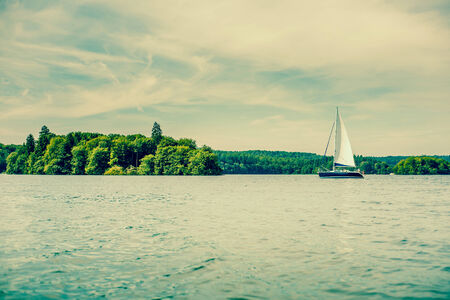 Small sailboat on an idyllic lake scenery photo