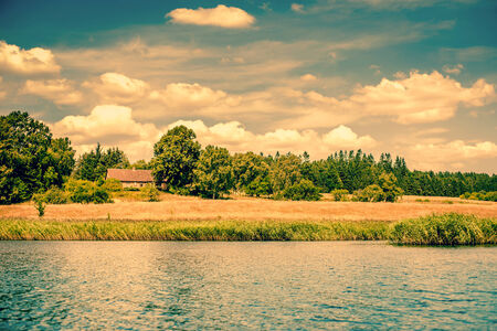 riverside trees: House by a riverside surrounded by fields and trees Stock Photo