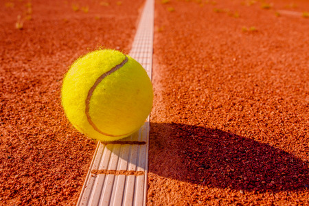 Yellow tennis ball touching the line on red clay court Stock Photo