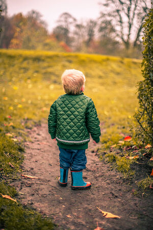 lonely boy: Lonely boy in a garden at autumn Stock Photo