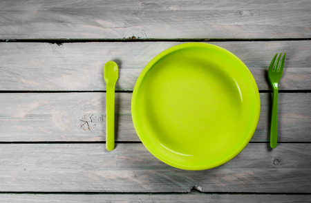 Green kids plate on wooden background Stock Photo