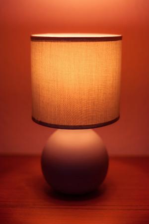 lit lamp: Lit lamp on a shelf in moody light Stock Photo