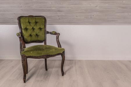 Chaise verte dans la conception victorienne sur le plancher en bois