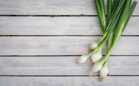 Scallions on a bright wooden table Stock Photo