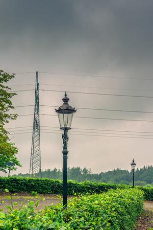 torres el�ctricas: L�mpara y torres de alta tensi�n en tiempo nublado Foto de archivo