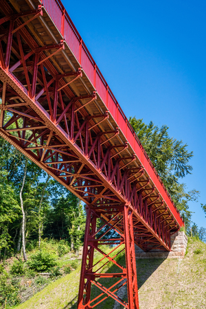 red metal: Old red metal bridge in perspective in the summertime Stock Photo
