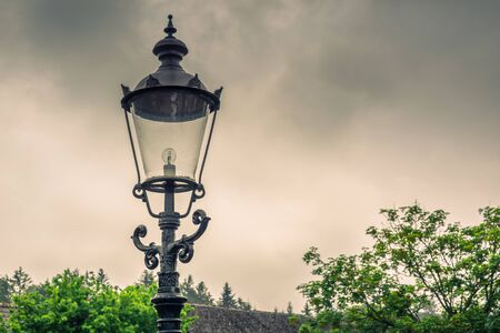 Vintage street lamp with a bulb in cloudy weather Banque d'images