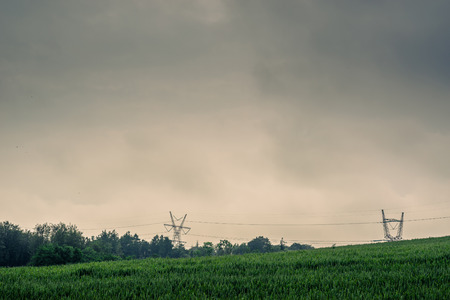 Pylons on a green field in cloudy weather Stock Photo