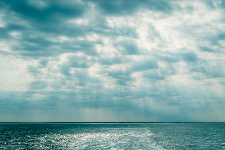peaceful background: Clouds over the ocean with sunbeams in daylight Stock Photo