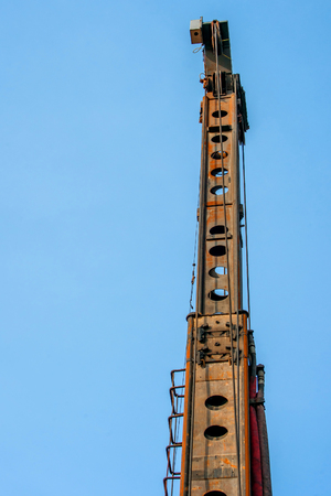 piling: Tall industrial piling machine isolated on blue background