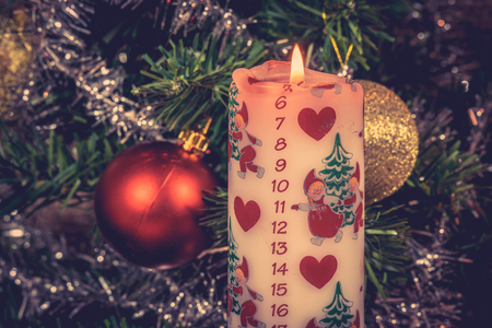White Christmas candle with a december calendar
