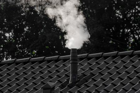 White smoke from a chimney on a house Standard-Bild