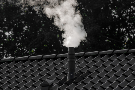 White smoke from a chimney on a house Stock Photo