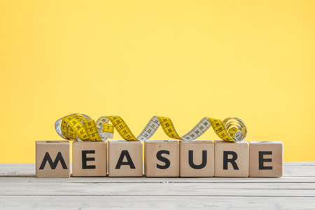 accomplishes: Measure tape on a wooden sign on a table Stock Photo