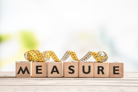 accomplishes: Measure word on a wooden table with measure tape