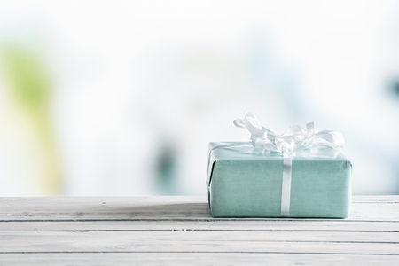 Blue gift box on a wooden table in bright light
