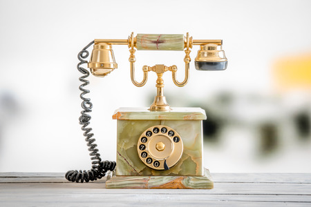 antique telephone: Antique telephone in gold and marble on a wooden desk