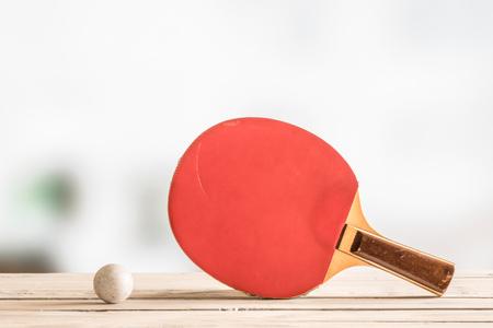 Tabla bate de tenis con una pelota en un escritorio de madera Foto de archivo - 54123575