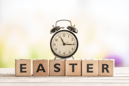 easter sign: Alarm clock on a wooden easter sign in a garden