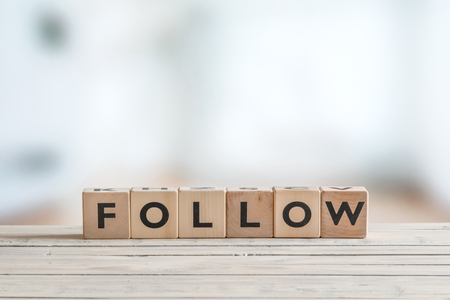 Follow sign made of cubes on a wooden table