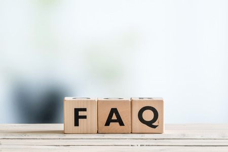 FAQ sign made of wood on an office table Stock Photo