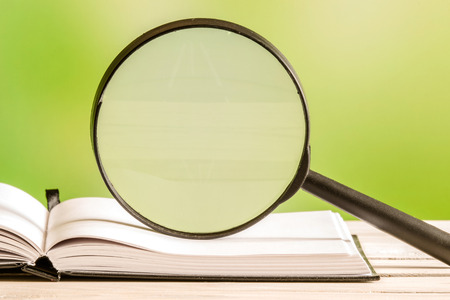 guidebook: Magnifying glass on an open book with green background